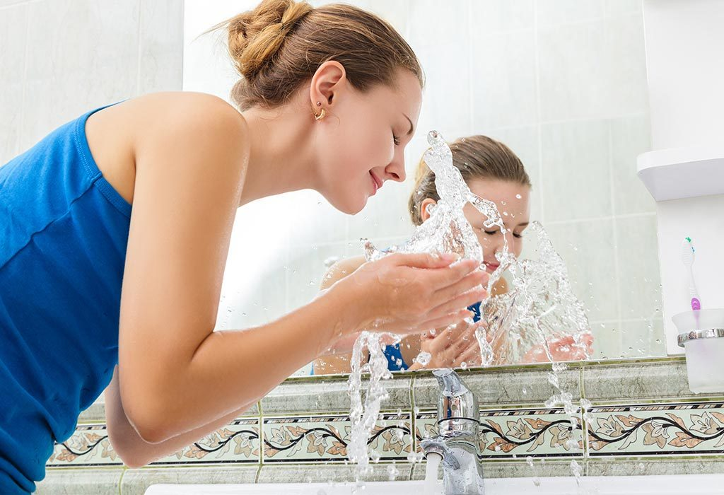Woman washing her face with plain water